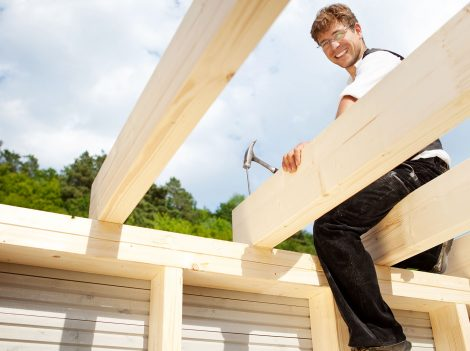 Happy carpenter sitting on the the roof beams and hammering a large nail